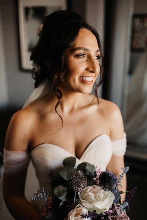 Off the shoulder dress with purple faux flower bouquet