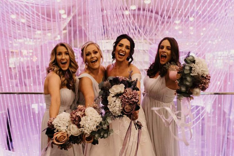 Bride and her bridesmaids with purple faux flower bouquets