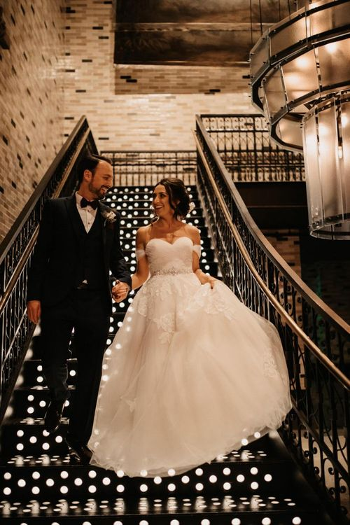 Bride and groom embrace in beautiful lace off the shoulder dress