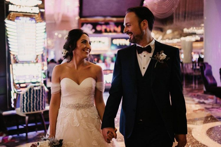 Bride and groom embrace in beautiful lace off the shoulder dress for Las Vegas wedding