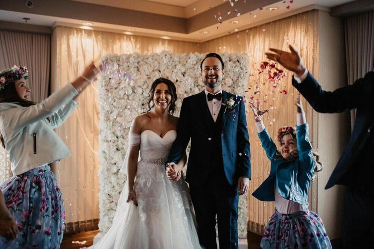 Bride and groom confetti shot with beautiful flower wall
