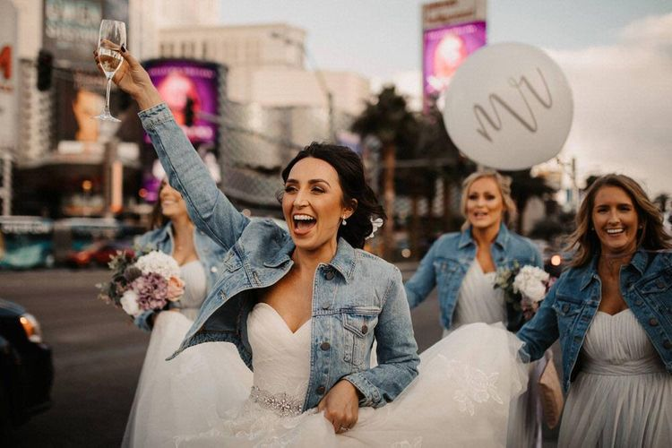 Bride with her bridal party wearing personalised denim jackets walking down the strip with balloons