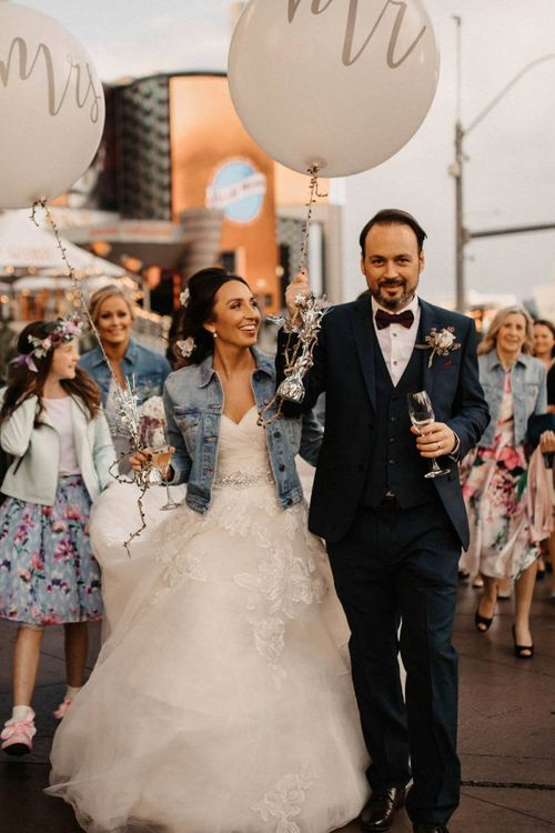 Bride and groom walk with their guests down the strip at Las Vegas wedding