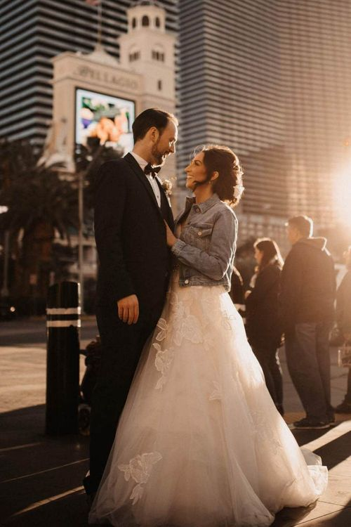 Bride and groom embrace wearing lace dress and personalised denim jacket