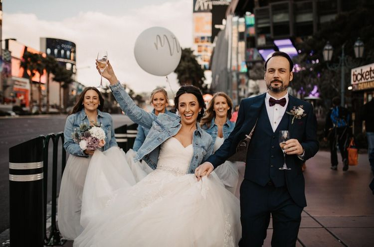 Bride and groom take a walk down the strip for a Las Vegas wedding with personalised denim jacket