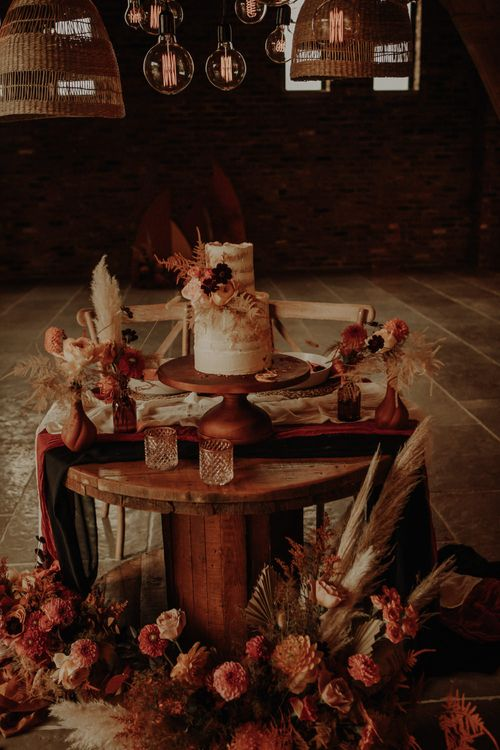 Semi naked wedding cake on a wooden cake stand