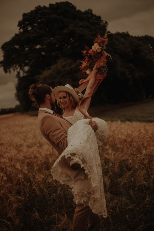 Groom picking his bride up in a corn field