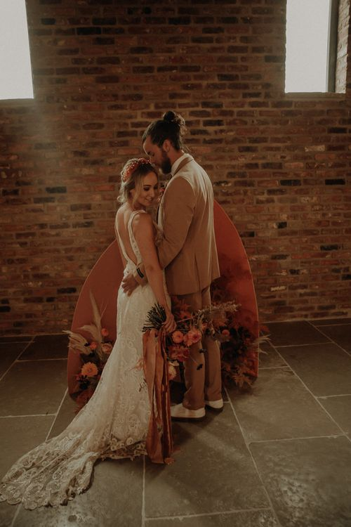 Bride and groom standing in front of an orange board and floral altar
