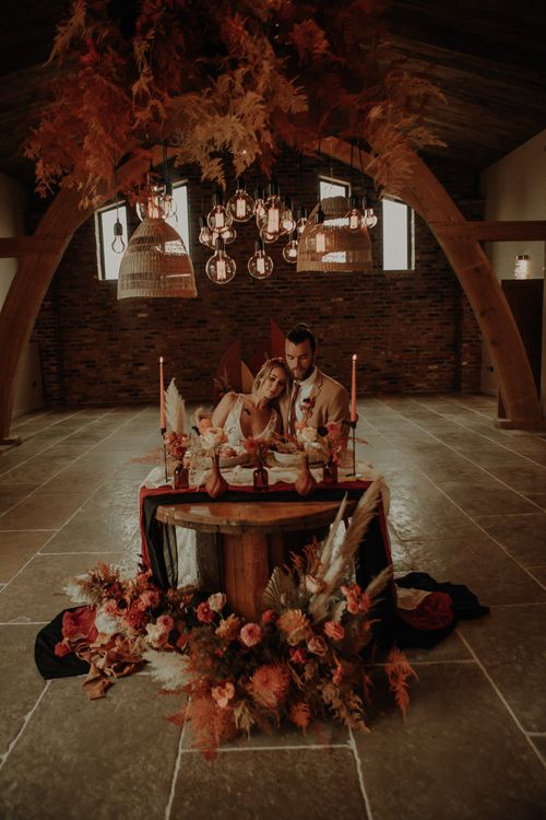 Bride and groom sitting at a cog wheel sweetheart table with light installation