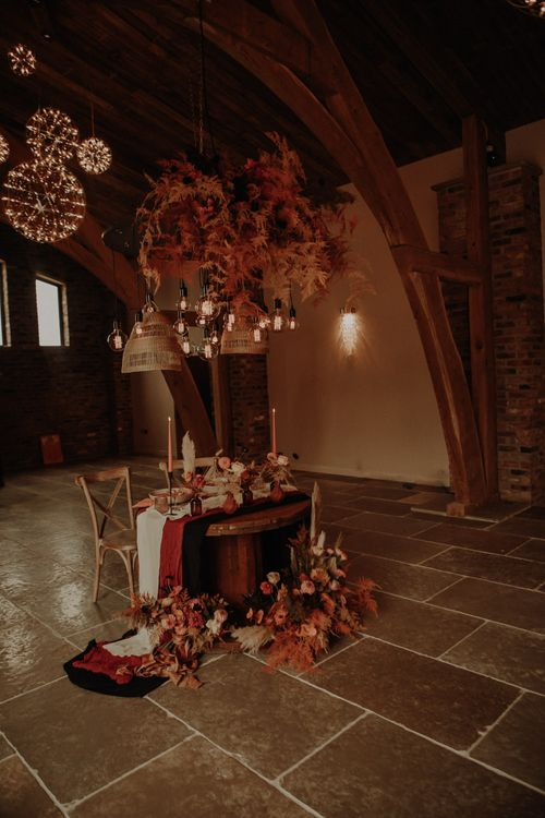 Sweetheart table with orange and neutral wedding flowers