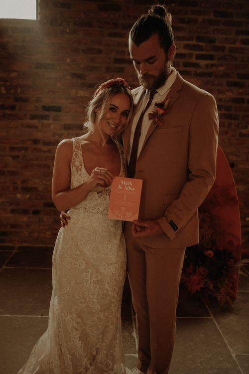 bride and groom holding an orange wedding invitation