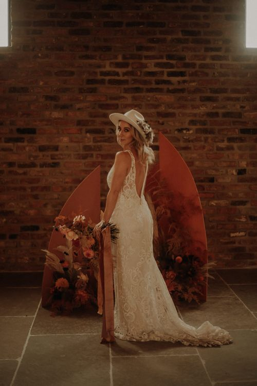 Bride in lace wedding dress standing in front of an orange board and floral altar