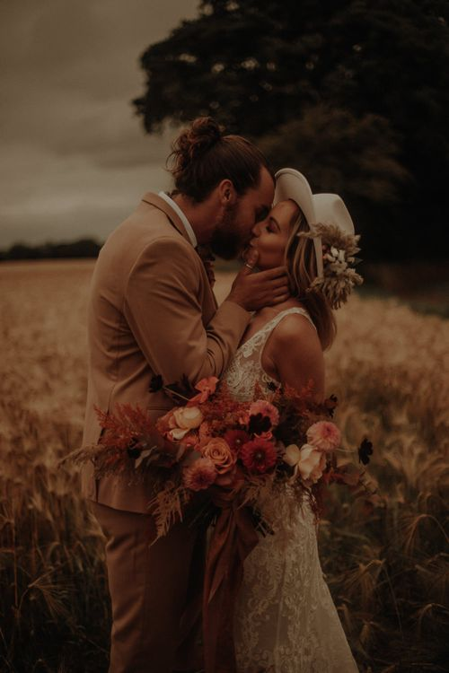 boho bride and groom with orange wedding flower bouquet