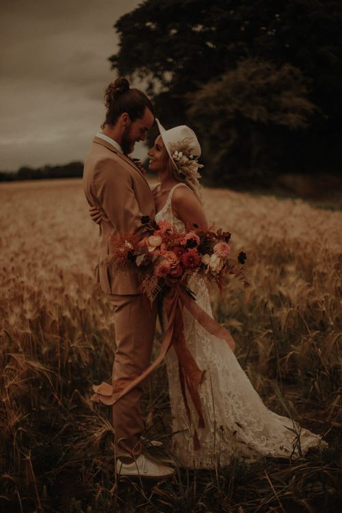 Bride in flower fedora hat and lace wedding dress