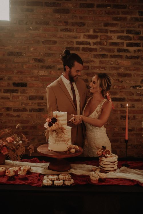 Bride and groom standing next to the dessert table