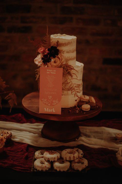 Semi naked wedding cake with orange sign and wood cake stand