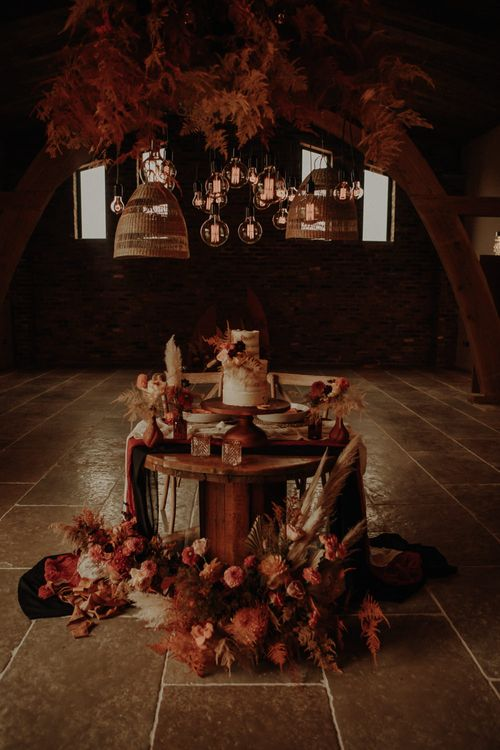 Cog wheel sweetheart table with wedding cake and flower decor