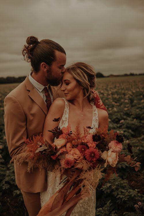 Groom in beige suit kissing his bride holding an orange flower bouquet