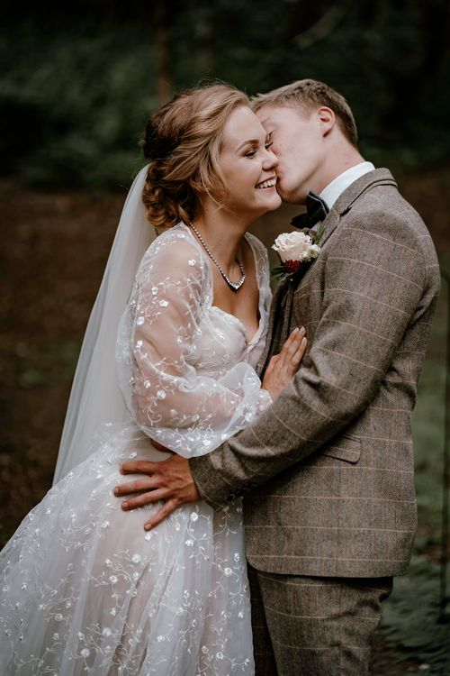 Groom in brown check suit kissing his bride at eco-friendly wedding