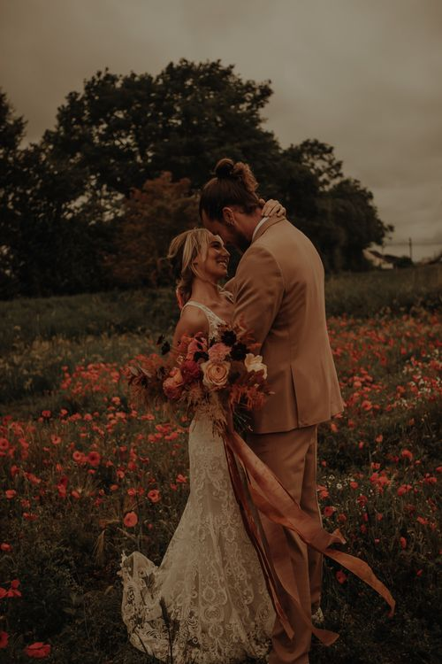 Bride and groom kissing in a poppy field